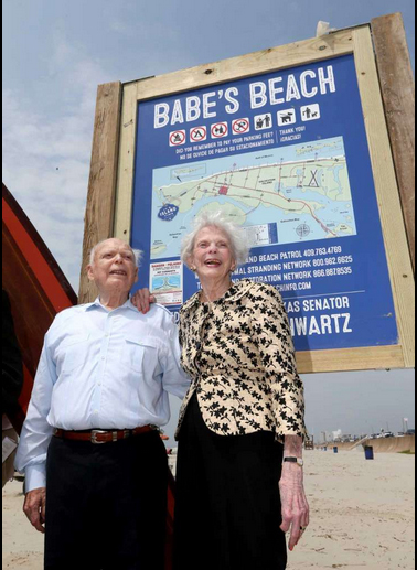 Senator Schwartz and his wife Marilyn stand by the sign for Galveston's Babe's Beach. Photo courtesy of Senator Schwartz.